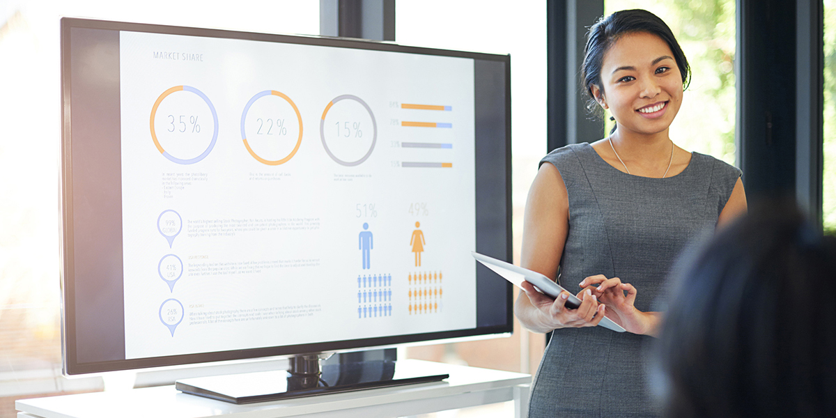 A marketer standing in front of a presentation screen with data on it