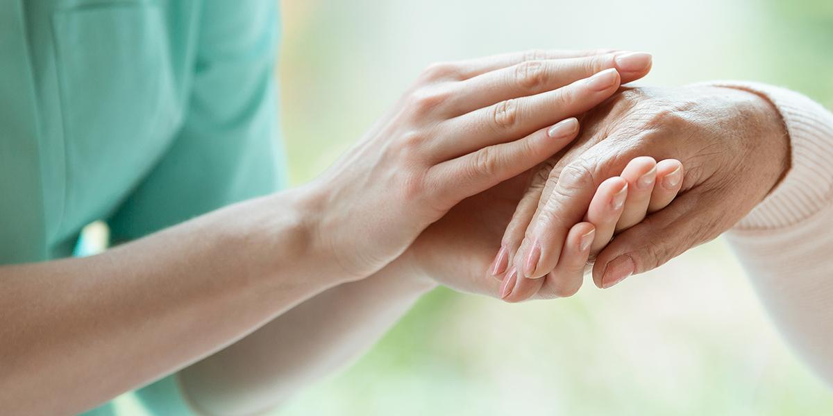 A caregiver holding the hand of a senior