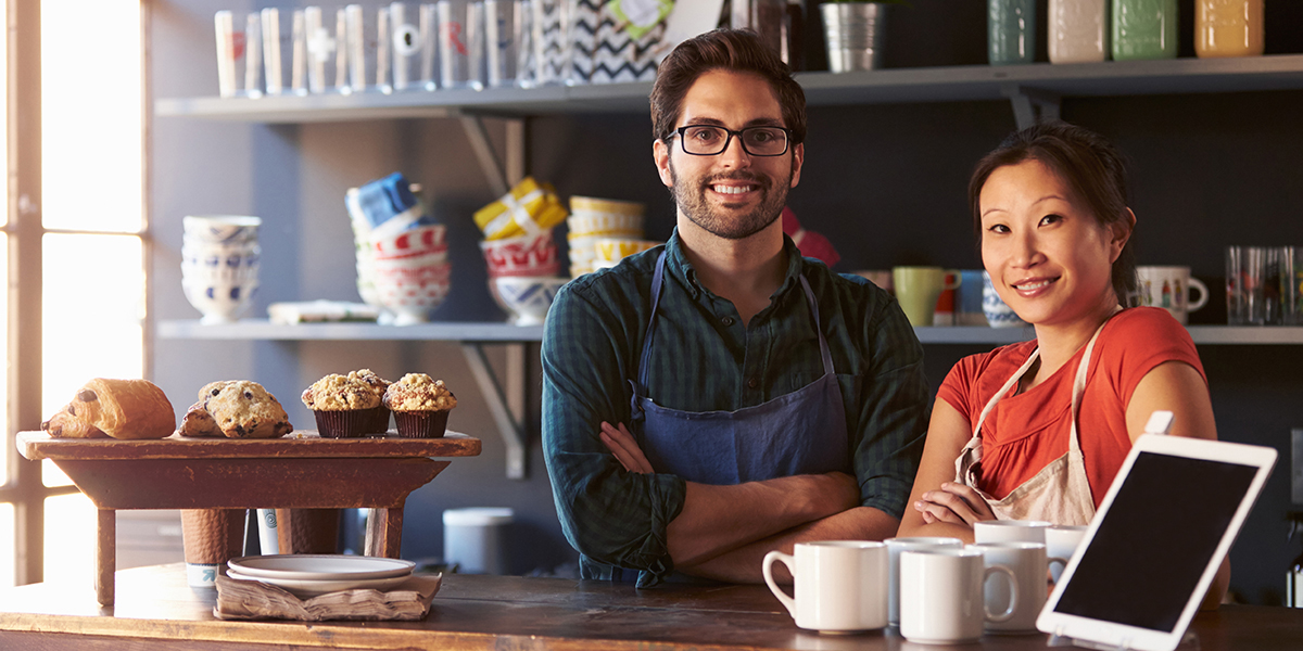 Two baristas behind the counter of a coffee shop