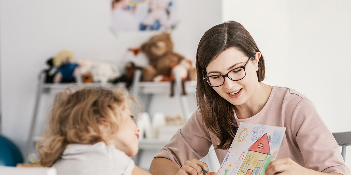 A child care worker reviewing a drawing with a child