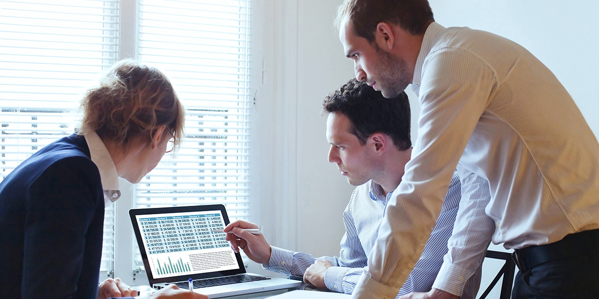 Three professionals standing in front of a laptop reviewing data in an office