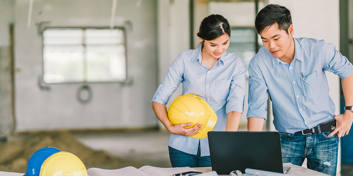 Two engineers with hard-hats reviewing a laptop