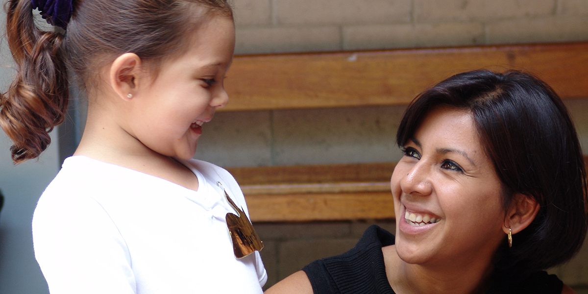 A lady smiling with a child