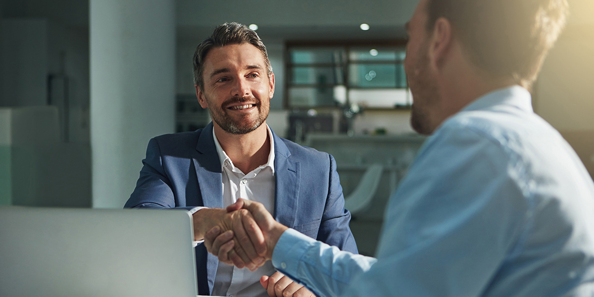 Two business people shaking hands in an office