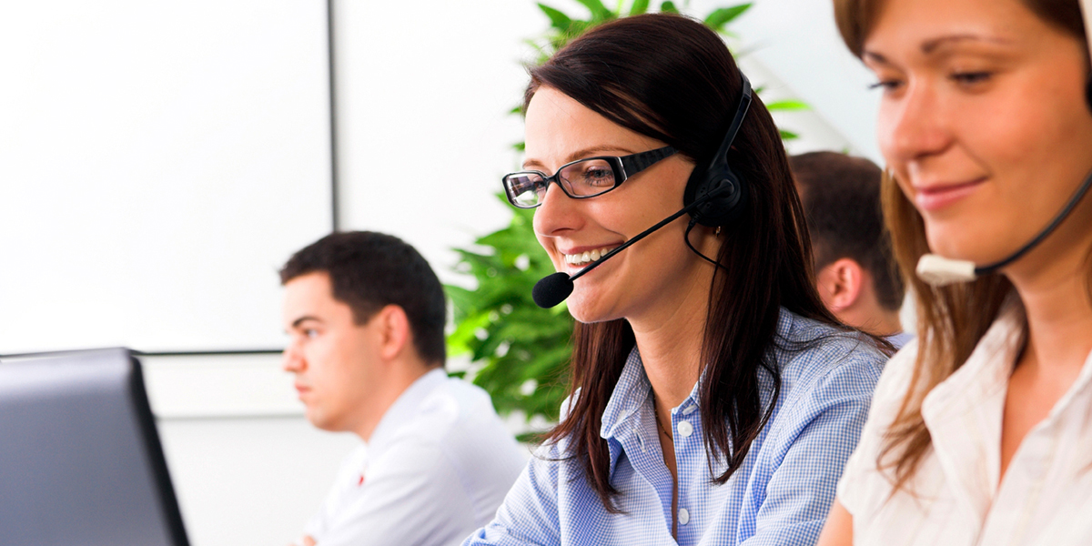Team members in a call center smiling with headphones on working on computers