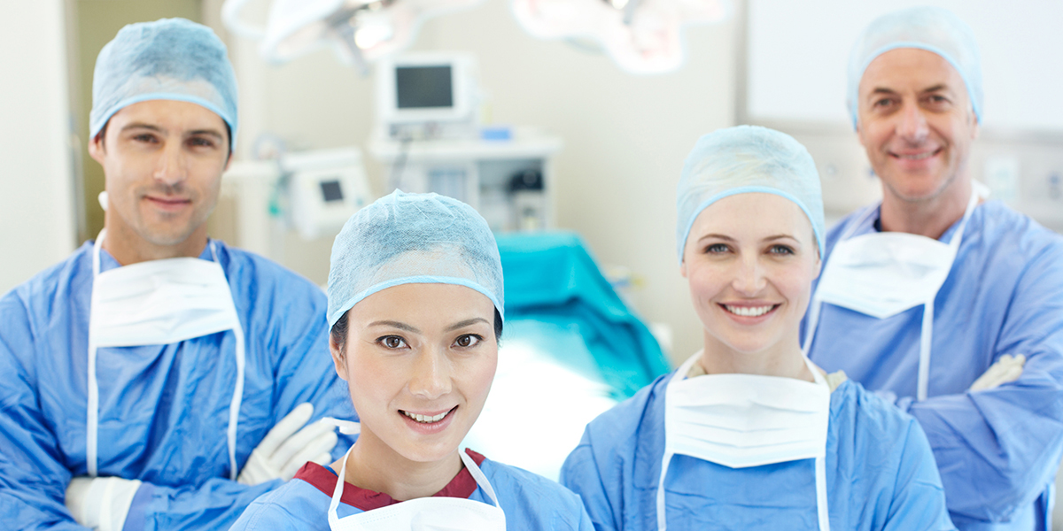 A team of medical staff in scrubs, masks, and medical gear