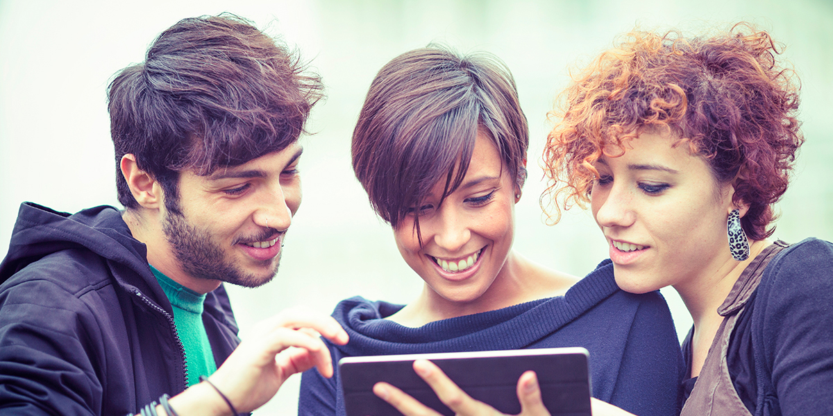Three friend reviewing data on a tablet