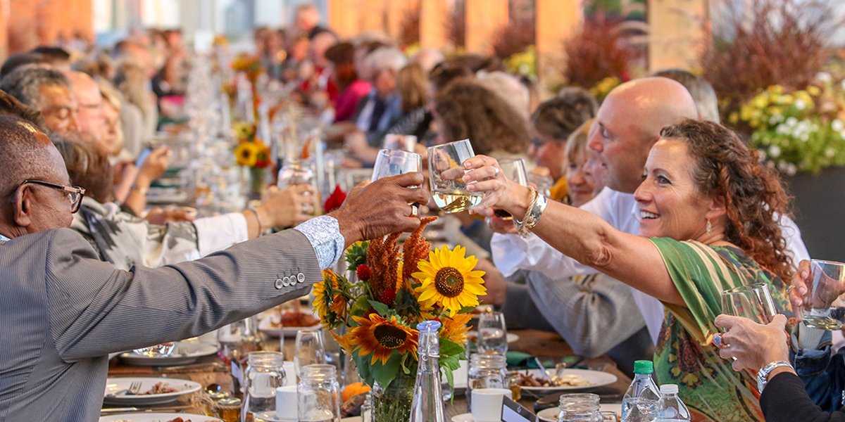 DC staff, alumni and guests make a toast at the fifth annual Harvest Dinner