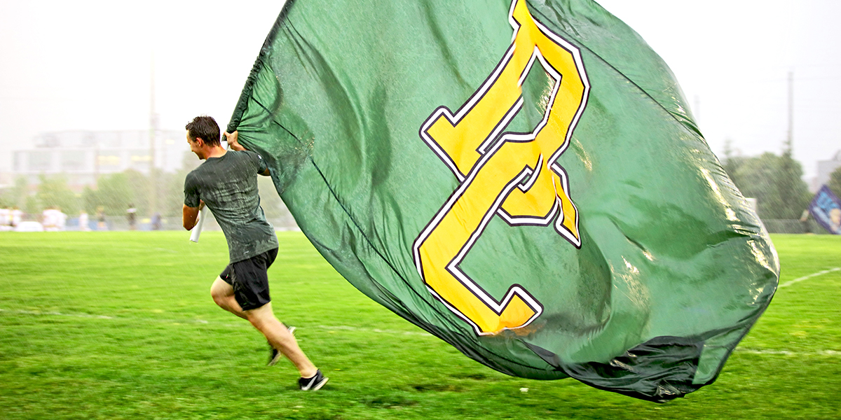 student waving the Durham College flag at the campus cup games