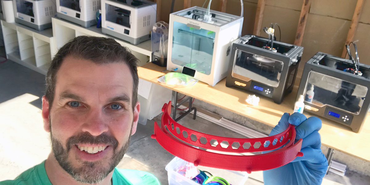 Male in front of several 3D printers