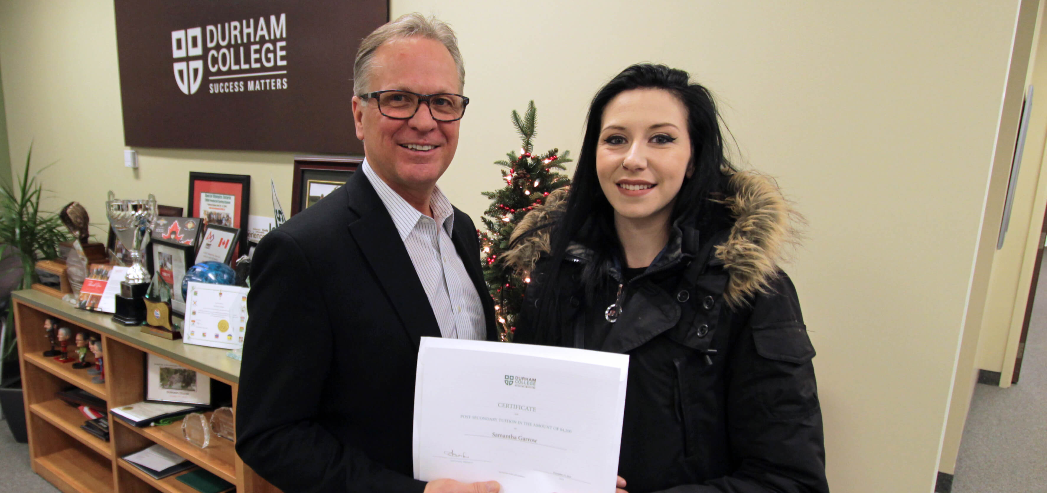 High school student Samantha Garrow is presented with a tuition certificate by DC President Don Lovisa