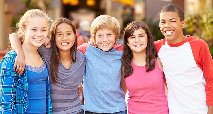Group Of Children Hanging Out Together In Mall Smiling To Camera