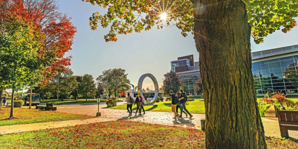 Oshawa campus looking toward bus loop area in the fall with students walking