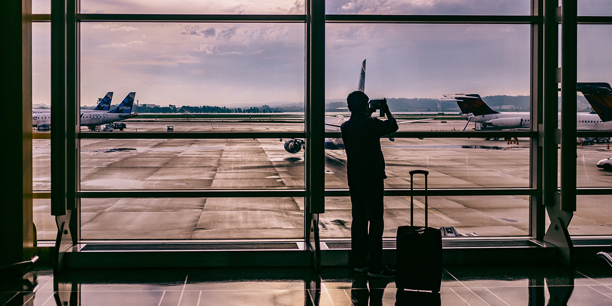 Person taking a picture of a plane at the airport