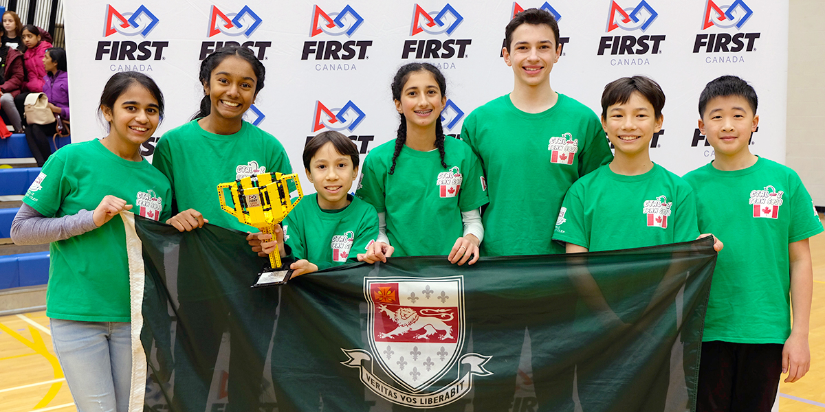 Bayview Glen team holding up banner and trophy - winners of the first lego league