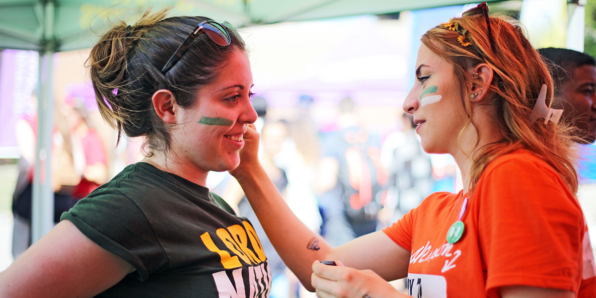 Student getting face paint done by another student during the first year fun fair