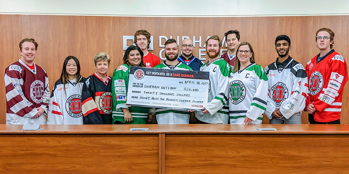 DC students pose for camera with a cheque for money raised.