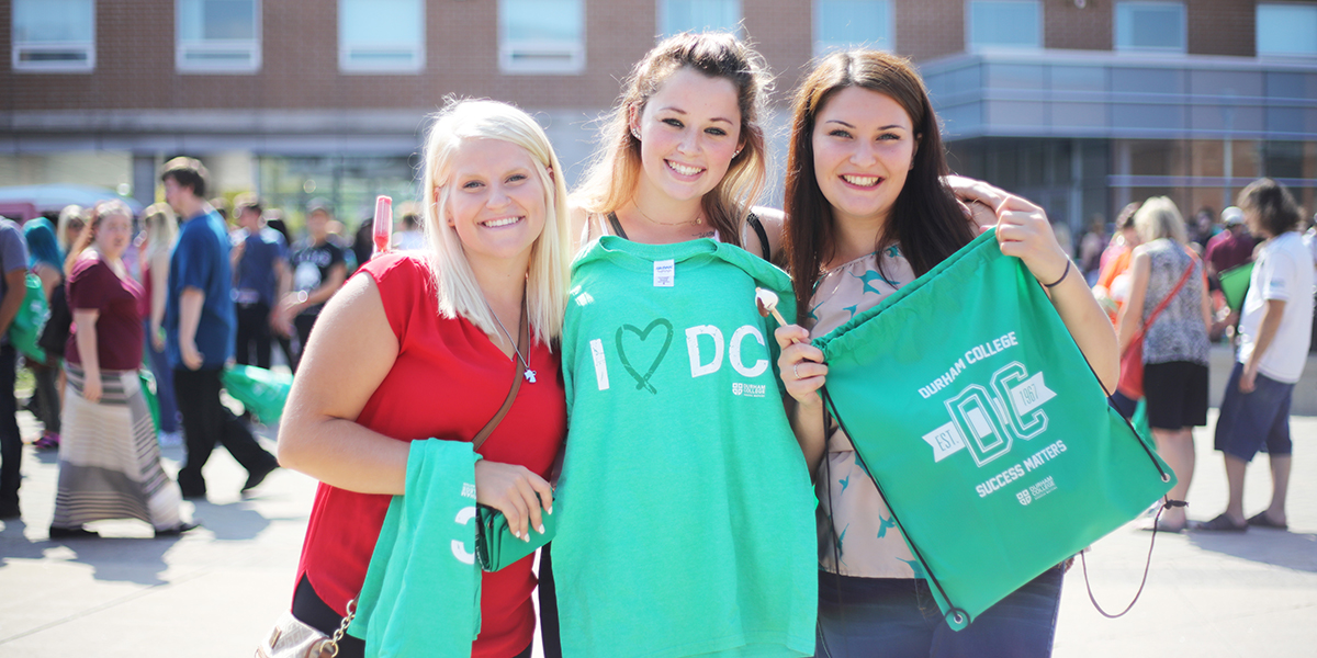 "Durham college students smiling hold ""I Love DC,"" merchandise"