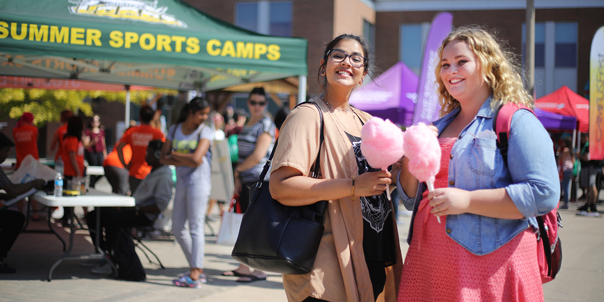 Students smiling at the first year fun fair with cotton candy in their hands